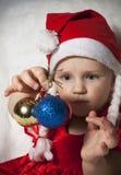 Criança pequena no chapéu do Natal com as decorações da árvore de Natal Fotografia de Stock Royalty Free