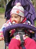 A criança pequena no chapéu e com chupeta senta-se na cadeira de rodas Foto de Stock