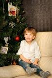 Criança pequena no sofá na árvore de Natal imagens de stock