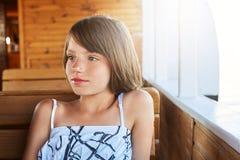 Criança pequena pensativa com o cabelo sacudido que descansa na plataforma de madeira, olhando de lado ao sonhar sobre algo Menin Imagem de Stock