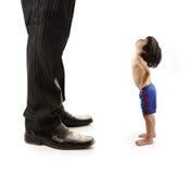 A criança pequena pequena está olhando os pés gigantes Imagem de Stock Royalty Free