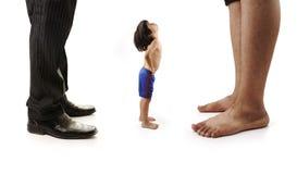 A criança pequena pequena está olhando os pés gigantes imagem de stock