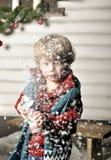 A criança pequena pressiona uma garrafa com neve artificial imagens de stock royalty free