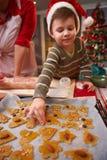 Criança pequena que ajuda com bolo do Natal Fotografia de Stock Royalty Free