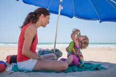 Criança pequena que bebe do bloco com a mãe na praia Foto de Stock