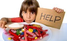 Criança pequena que come o açúcar doce no prato dos doces que guarda o spoo do açúcar Foto de Stock Royalty Free
