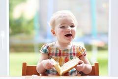 Criança pequena que come o pão com manteiga Fotografia de Stock
