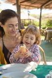 Criança pequena que come o pão que senta-se nos pés da mulher Fotos de Stock
