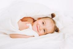 Criança pequena que encontra-se na cama em casa 2 anos de restos velhos do bebê sob a cobertura branca Imagens de Stock Royalty Free