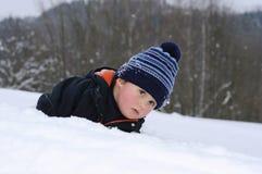 Criança pequena que encontra-se na neve imagem de stock royalty free