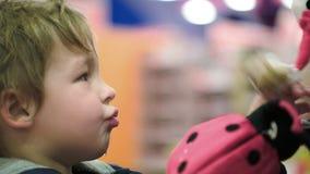 Criança pequena que escolhe brinquedos macios na loja video estoque