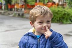 Criança pequena que escolhe seu nariz e que faz as caras foto de stock royalty free