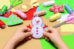 Criança pequena que guarda um boneco de neve do Natal de feltro nas mãos A criança mostra ofícios do ornamento do Natal Local de  fotografia de stock royalty free