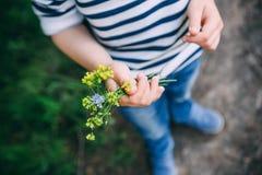 Criança pequena que guarda wildflowers de um ramalhete em sua mão foto de stock royalty free