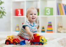 Criança pequena que joga com carros do brinquedo Menino da criança que senta-se no assoalho em casa imagens de stock royalty free
