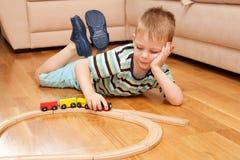 Criança pequena que joga com estrada de ferro de madeira imagem de stock