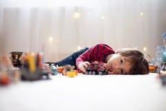 Criança pequena que joga com lotes dos brinquedos plásticos coloridos internos Imagem de Stock Royalty Free