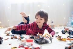 Criança pequena que joga com lotes dos brinquedos plásticos coloridos internos Foto de Stock Royalty Free