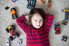 Criança pequena que joga com lotes dos brinquedos plásticos coloridos internos Fotos de Stock Royalty Free