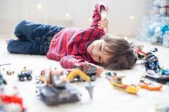 Criança pequena que joga com lotes dos brinquedos plásticos coloridos internos Fotografia de Stock