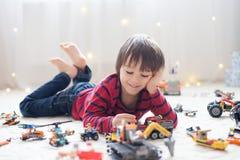 Criança pequena que joga com lotes dos brinquedos plásticos coloridos internos Fotografia de Stock Royalty Free