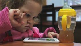 Criança pequena que joga com o telefone vídeos de arquivo