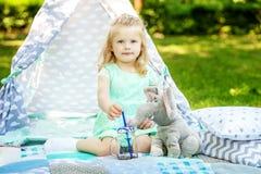 Criança pequena que joga com um brinquedo em um piquenique O conceito dos lifes imagem de stock royalty free