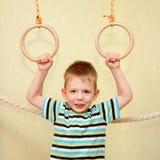 Criança pequena que joga esportes em anéis ginásticos foto de stock royalty free