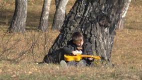 A criança pequena que joga na guitarra, resto do menino na árvore, aprecia o som video estoque