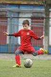 Criança pequena que joga o futebol ou o futebol Fotos de Stock Royalty Free