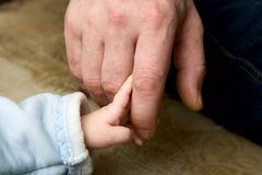 A criança pequena que mantem-se para um dedo do pai foto de stock royalty free