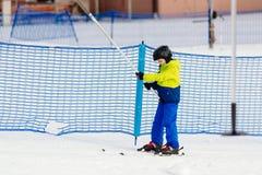 Criança pequena que vai acima a inclinação do esqui no elevador de esqui Fotografia de Stock