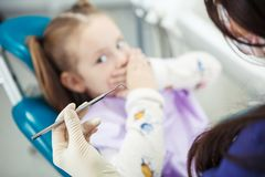 A criança pequena receosa do procedimento médico senta-se na cadeira do dentista Foto de Stock