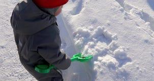 A criança pequena recolhe a pá verde da neve video estoque