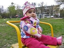 A criança pequena senta-se no carrossel Imagem de Stock