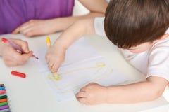 A criança pequena talentoso tira a imagem, tem o interesse à arte, guarda o marcador colorido, gosta de tirar, sua mãe ajuda-o Sp Fotos de Stock