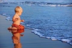 A criança pequena tem um divertimento na praia preta do mar do por do sol da areia foto de stock