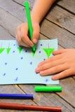 A criança pequena tira árvores e flocos de neve de Natal no papel imagens de stock royalty free