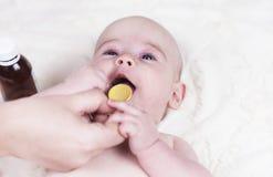a criança pequena, um bebê no escritório do doutor e são dados uma medicina para tossir e alergias de uma colher imagem de stock