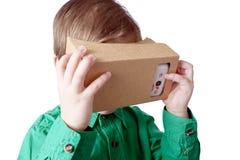 A criança pequena usa a realidade virtual (cartão de VR) no fundo branco Fotografia de Stock