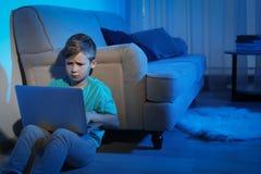 Criança pequena virada com portátil Perigo do Internet imagem de stock