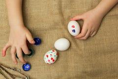 A criança pinta ovos para a Páscoa fotografia de stock