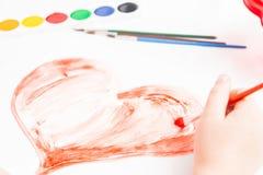 A criança pinta um coração Fotos de Stock Royalty Free