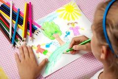 A criança pinta uma imagem dos lápis sobre a natureza de proteção fotografia de stock royalty free