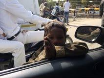 A criança pobre indiana reza ao carro dentro dos povos diz dá-me por favor o dinheiro imagem de stock royalty free