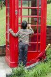 Criança por uma caixa do telefone de Brithish fotos de stock royalty free
