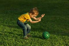 Criança positiva bonito, jogando felizmente com a bola no prado verde Imagens de Stock