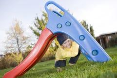 A criança positiva de sorriso senta-se sob a corrediça na grama Imagens de Stock Royalty Free