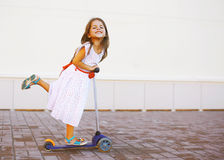 Criança positiva feliz no vestido no 'trotinette' na cidade Fotografia de Stock