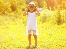 A criança positiva olha nos binóculos Imagem de Stock
